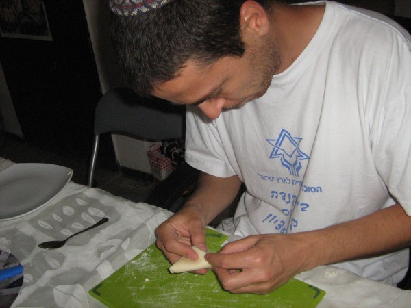 Gab preparing Shavuot cheese pastelles by folding them