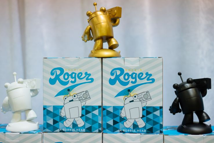 A trio of Roger figurines, one white, one gold, and one black